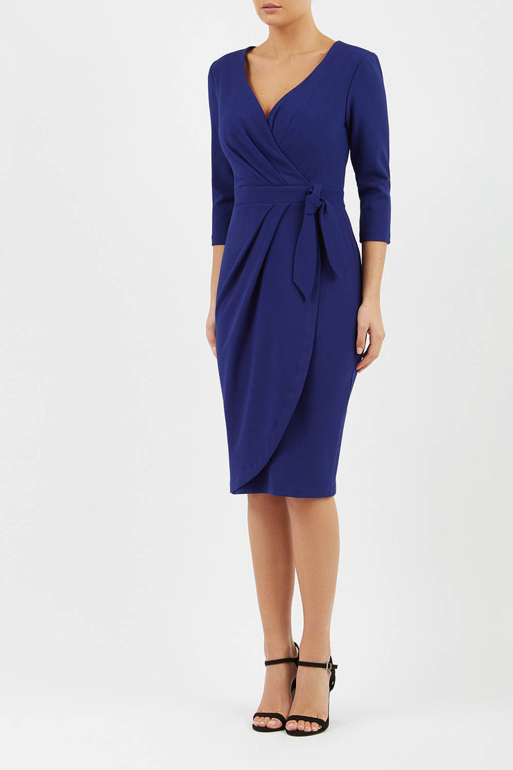 model wearing diva catwalk elan elegant dress with 3 4 sleeves with a tie detail and asymmetrical closing in navy blue colour front