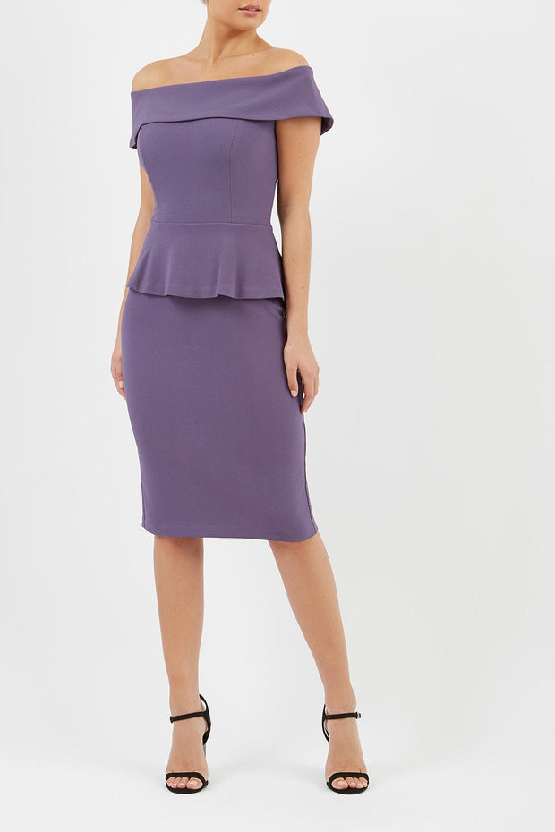 blonde model wearing diva catwalk peplum pencil skirt dress in mauve colour off shoulder bardot neckline front