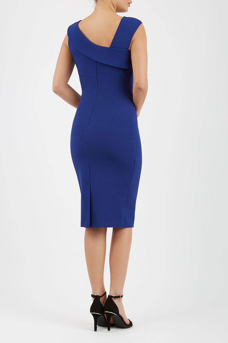 brunette model wearing diva catwalk rosita pencil skirt fitted dress with asymmetric neckline and bow detail at the top and it is a sleeveless design  with empire waistline in navy blue back