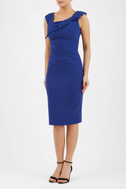 brunette model wearing diva catwalk rosita pencil skirt fitted dress with asymmetric neckline and bow detail at the top and it is a sleeveless design  with empire waistline in navy blue colour front