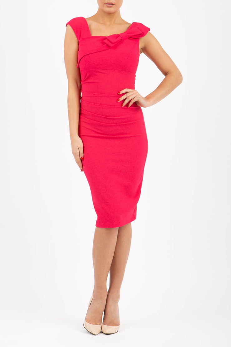 brunette model wearing diva catwalk rosita pencil skirt fitted dress with asymmetric neckline and bow detail at the top and it is a sleeveless design  with empire waistline in pink colour front