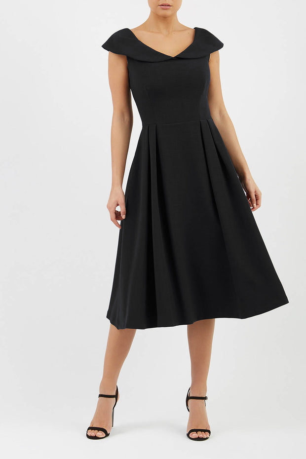 Model wearing the Diva Chesterton Sleeveless dress with oversized collar detail and swing pleated skirt in black front image