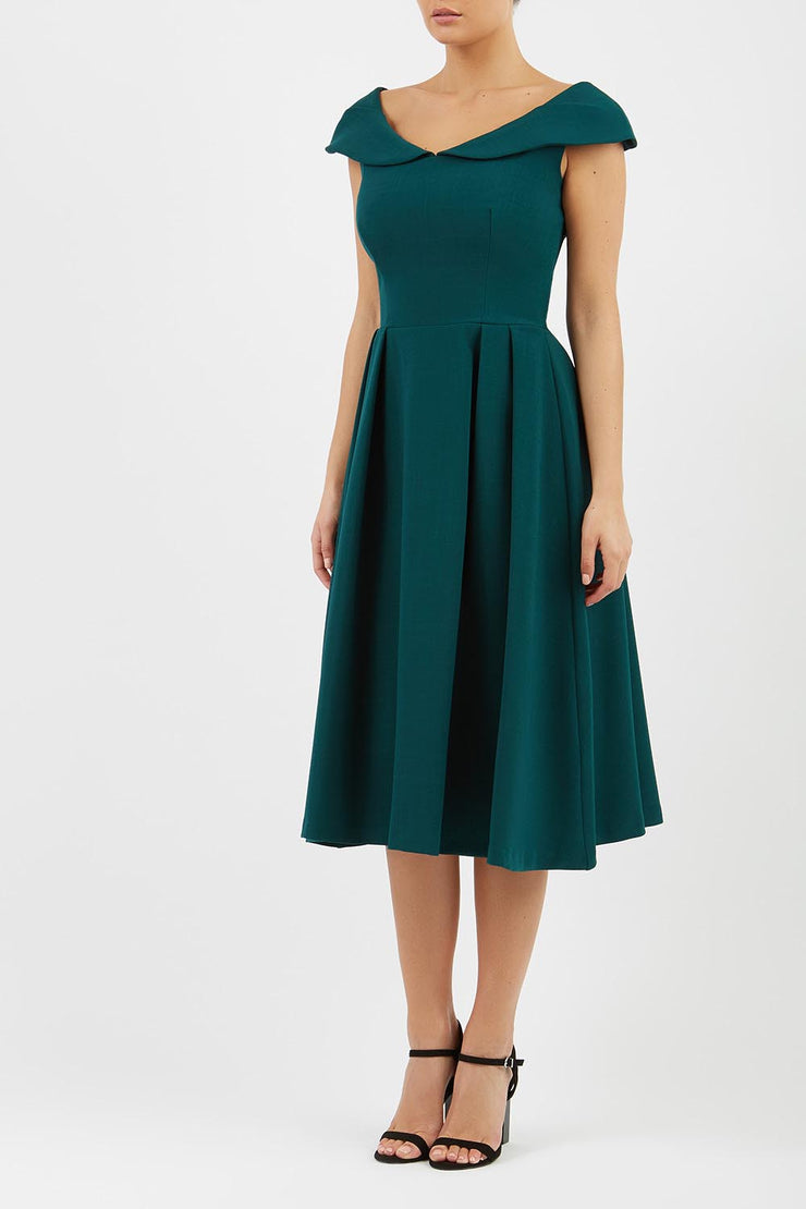 Model wearing the Diva Chesterton Sleeveless dress with oversized collar detail and swing pleated skirt in forest green front image
