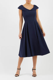Model wearing the Diva Chesterton Sleeveless dress with oversized collar detail and swing pleated skirt in navy front image