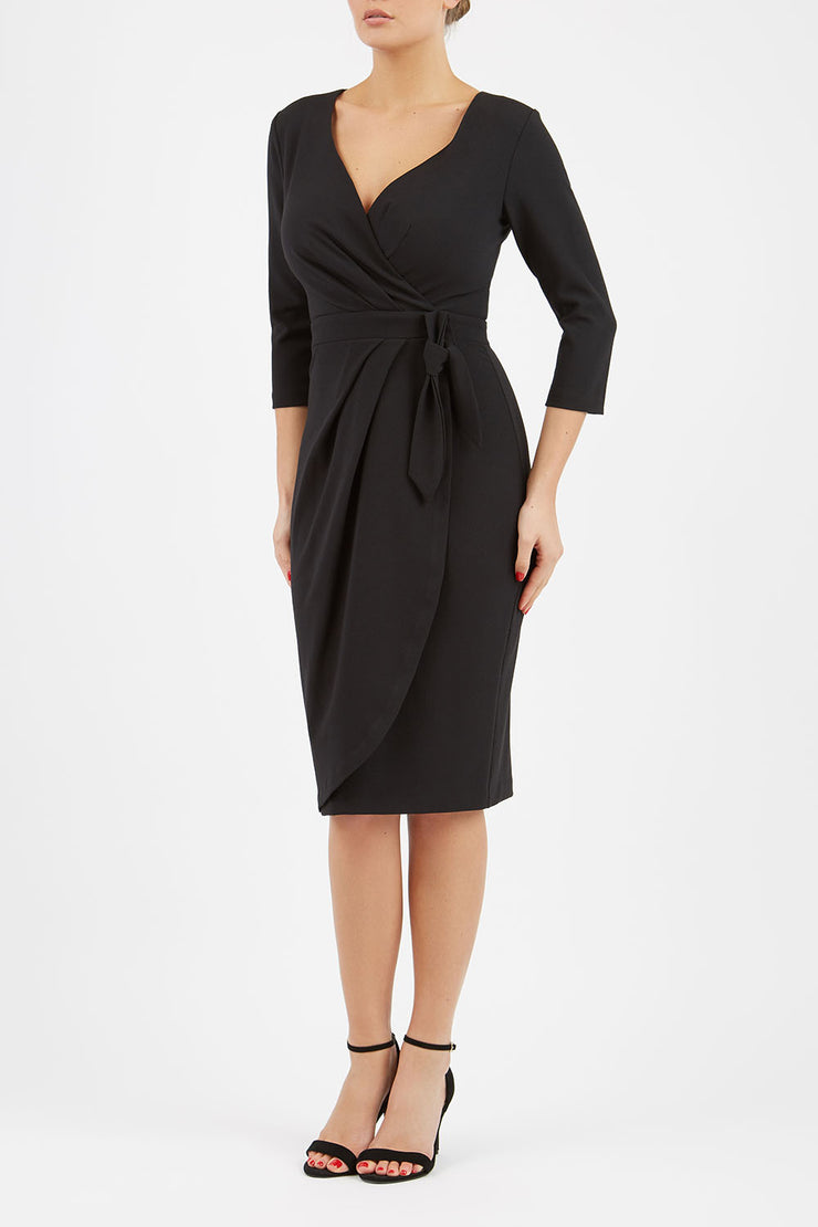 model wearing diva catwalk elan elegant black dress with 3 4 sleeves with a tie detail and asymmetrical closing front