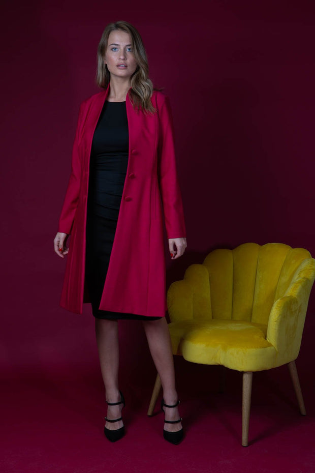 brunette model wearing diva catwalk couture fine raquella coat with buttons across the front and long sleeves with high neck and pockets in crimson pink colour front