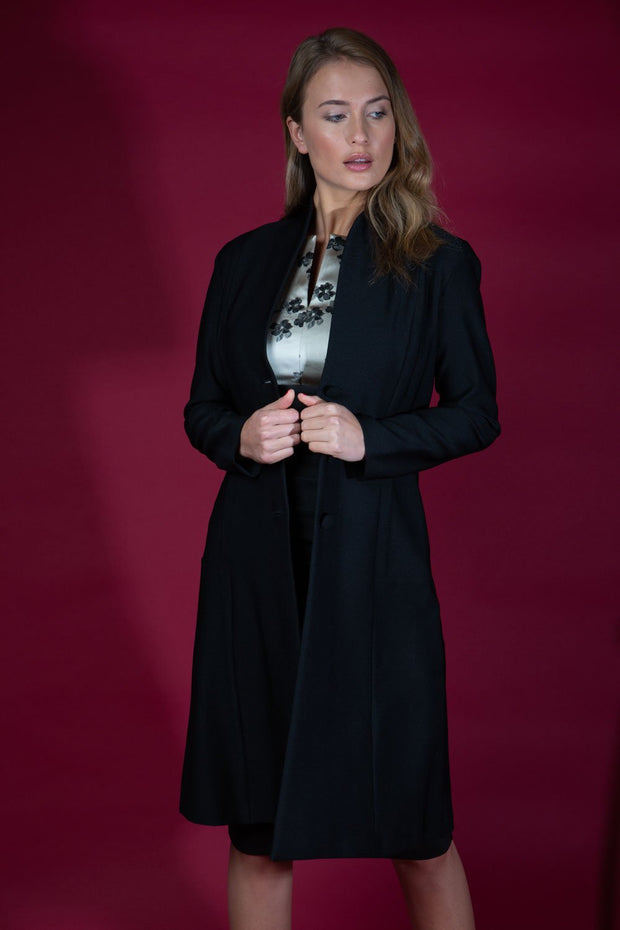 brunette model wearing diva catwalk couture fine raquella coat with buttons across the front and long sleeves with high neck and pockets in black colour front