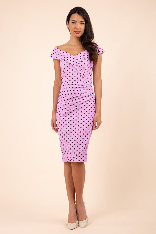Brunette model wearing Diva Catwalk Fenella Polka Dot Pencil Sleeveless Dress off shoulder bardot neckline in pink front