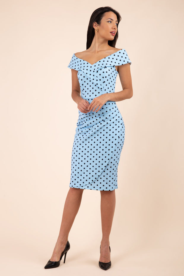 Brunette model wearing Diva Catwalk Fenella Polka Dot Pencil Sleeveless Dress off shoulder bardot neckline in blue front