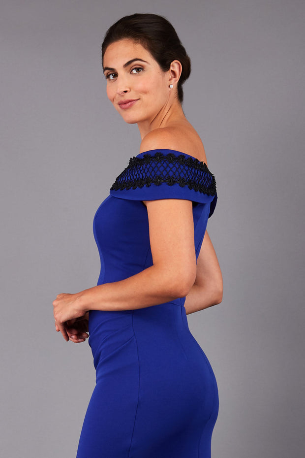 brunette model wearing diva catwalk kurumba pencil dress with bardot off shoulder neckline and lace detail across it in cobalt blue and black colour front