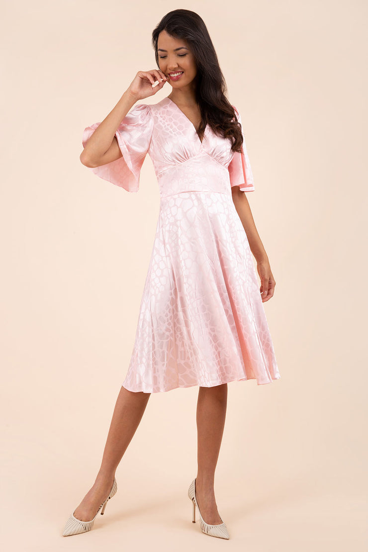 brunette model wearing diva catwalk cambrian satin swing dress with bell short sleeve wide asymmetric waistband and pleating under bust in pink front
