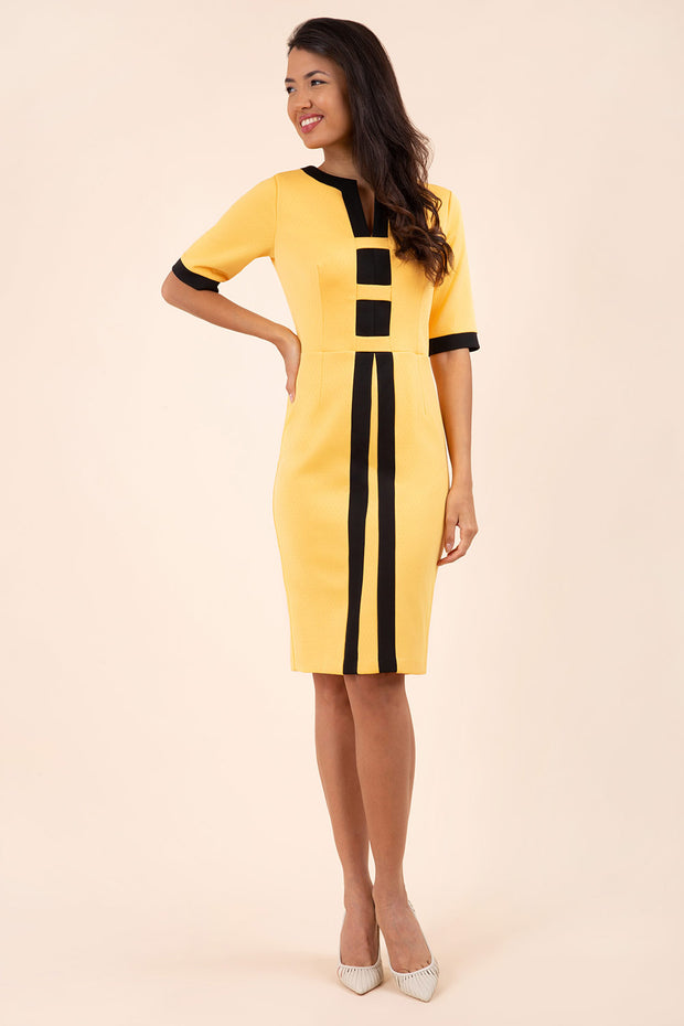 brunette model wearing Diva catwalk goggle pencil dress with short sleeve and v-neckline with contrasted design across body in yellow front