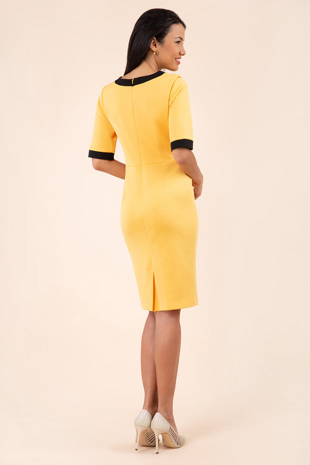 brunette model wearing Diva catwalk goggle pencil dress with short sleeve and v-neckline with contrasted design across body in yellow back
