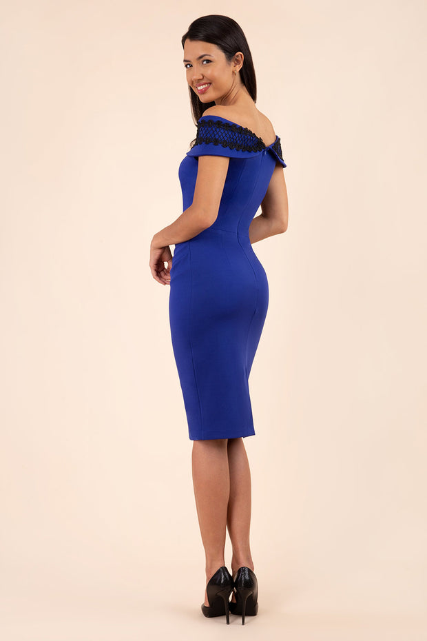 Model wearing  Diva catwalk Kurumba pencil dress sleeveless with pleating across the body in cobalt blue with black lace trim detailing back