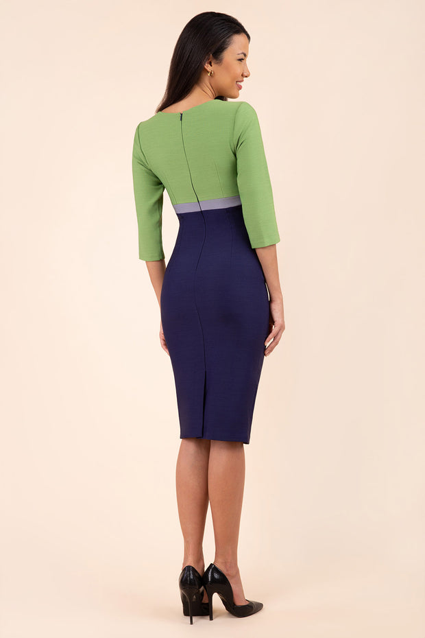 brunette model wearing seed lara pencil colour block dress three quarter sleeve and pleating across the body with split neckline in navy blue and citrus green and sky grey back