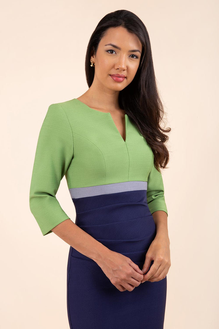 brunette model wearing seed lara pencil colour block dress three quarter sleeve and pleating across the body with split neckline in navy blue and citrus green and sky grey front