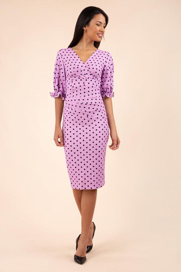 brunette model wearing diva catwalk palacio pencil fitted dress with three quarter puffed sleeve and pleating across the body with overlapping v-neckline in pink polka dot front