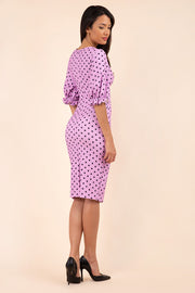 brunette model wearing diva catwalk palacio pencil fitted dress with three quarter puffed sleeve and pleating across the body with overlapping v-neckline in pink polka dot back