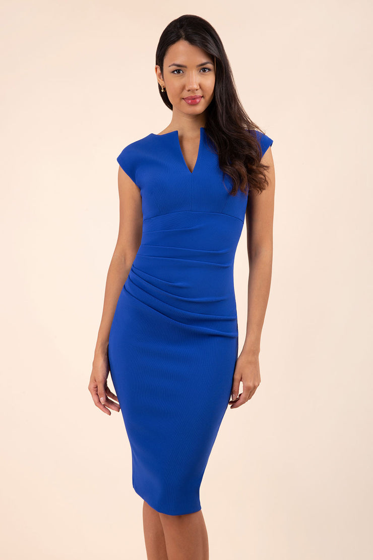 brunette model wearing diva catwalk lydia sleeveless pencil flattering fitted plain dress with split neckline and pleating across the body cobalt blue front