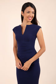 brunette model wearing diva catwalk lydia sleeveless pencil flattering fitted plain dress with split neckline and pleating across the body in navy blue front