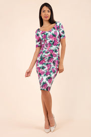 brunette model is wearing diva ctawalk paradise palm print pencil fitted dress with sweetheart neckline and rushing at the front with short sleeve front