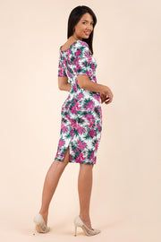 brunette model is wearing diva ctawalk paradise palm print pencil fitted dress with sweetheart neckline and rushing at the front with short sleeve back