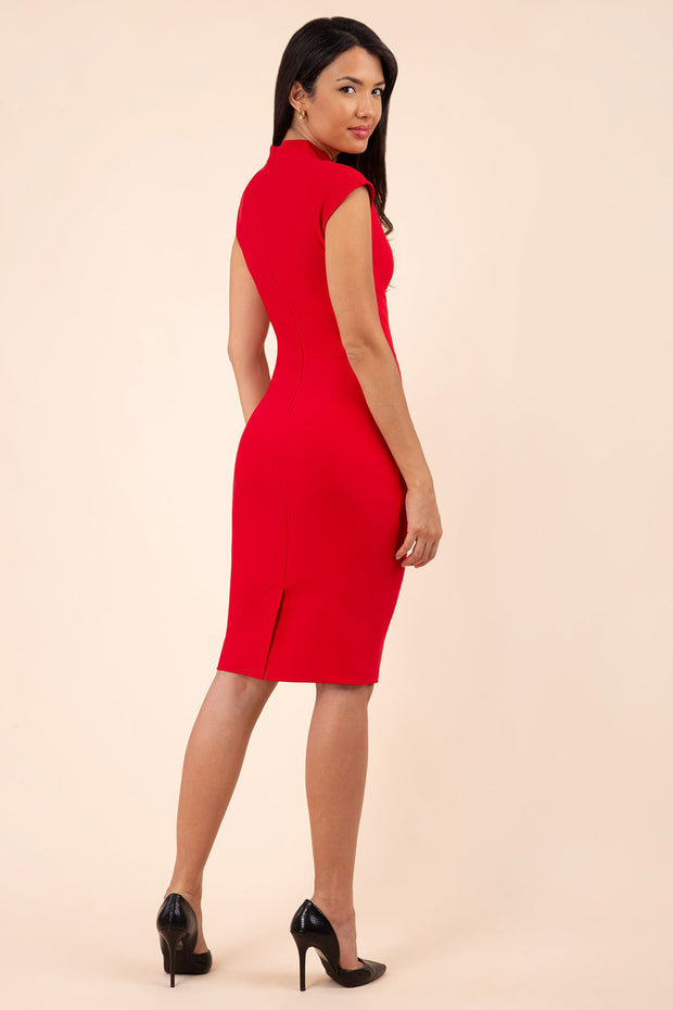 brunette model wearing diva catwalk beyonce pencil fitted dress with high neckline without sleeves with a wide band and pleating across the tummy area with a crossed detail neckline in scarlet red back