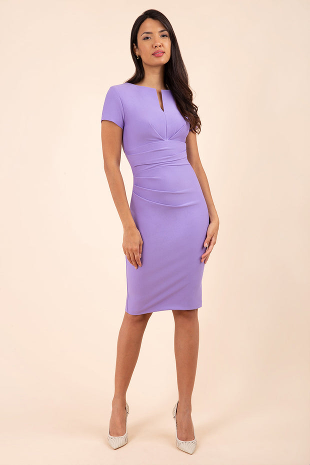 model wearing diva catwalk donna pencil dress in colour lilac wisteria with wide band and sleeves and rounded neckline with low split in front