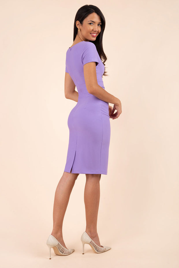 model wearing diva catwalk donna pencil dress in colour lilac wisteria with wide band and sleeves and rounded neckline with low split in front back