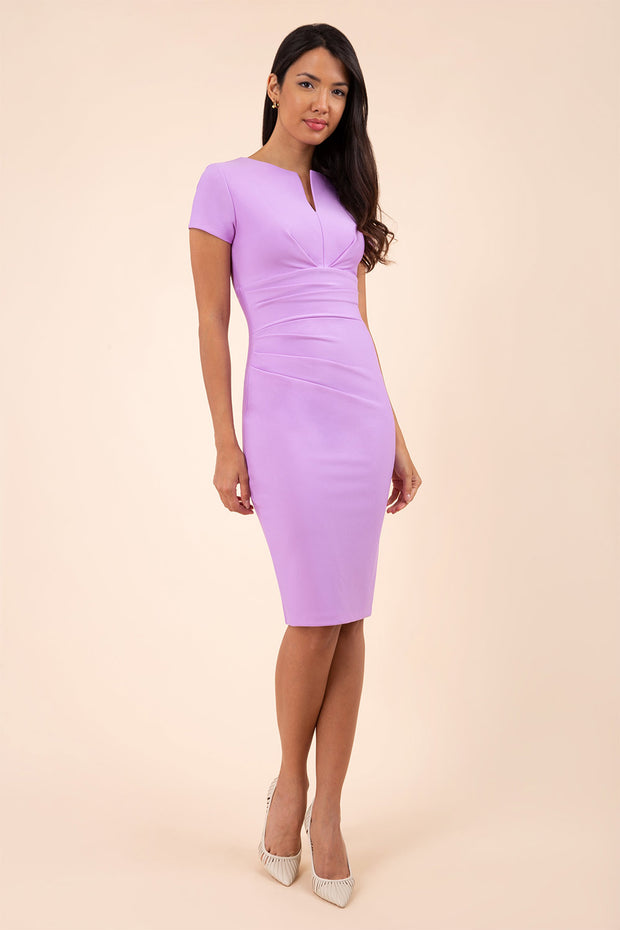 model wearing diva catwalk donna pencil dress in pale lilac colour with wide band and sleeves and rounded neckline with low split in front