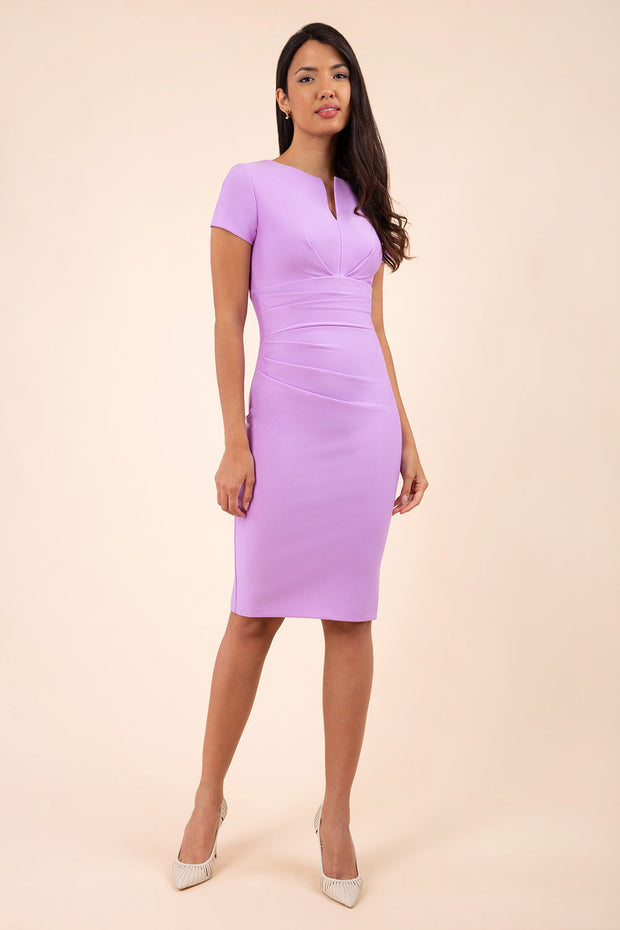 model wearing diva catwalk donna pencil dress in colour violet bloom with wide band and sleeves and rounded neckline with low split in front