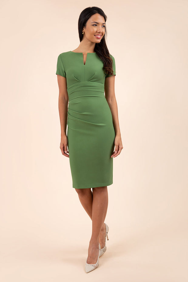 model wearing diva catwalk donna pencil dress in colour apple green with wide band and sleeves and rounded neckline with low split in front
