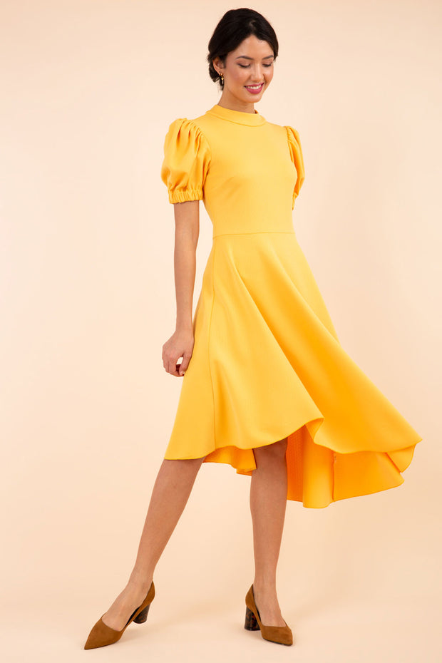 brunette model wearing diva catwalk ola swing dress with puffed oversized sleeves and asymmetric swing skirt with rounded high neck in yellow front