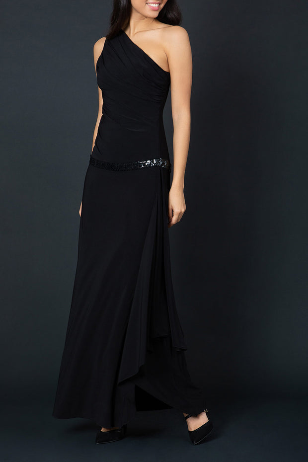 Model wearing Temptress Full length Sleeveless Asymmetric One shoulder A-line Swing dress with sparkling band detail across the waist area in black front