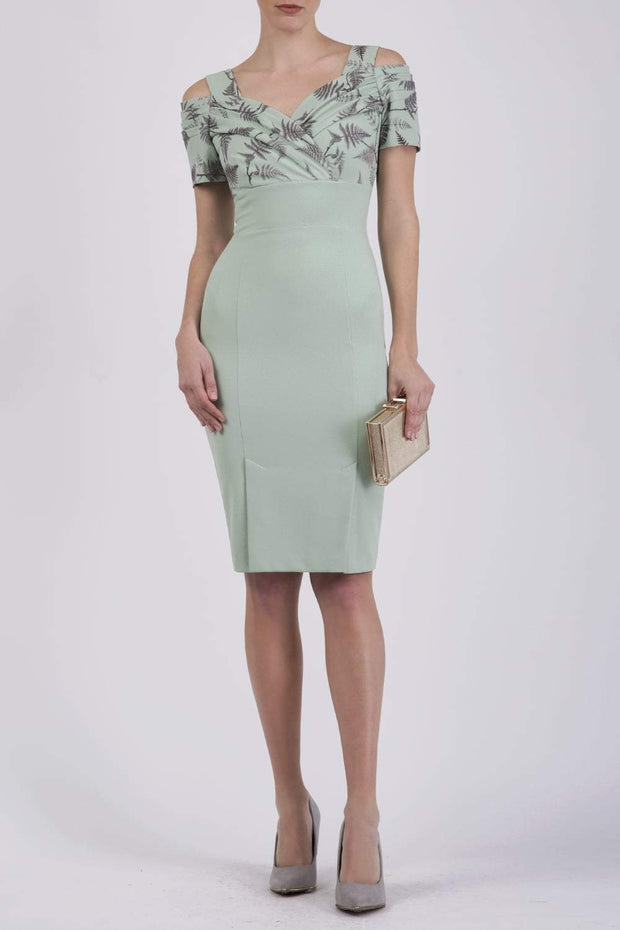 Model wearing the Diva Amorette pencil dress with cold shoulder and pleated detailing on the arms in deco green fern front image