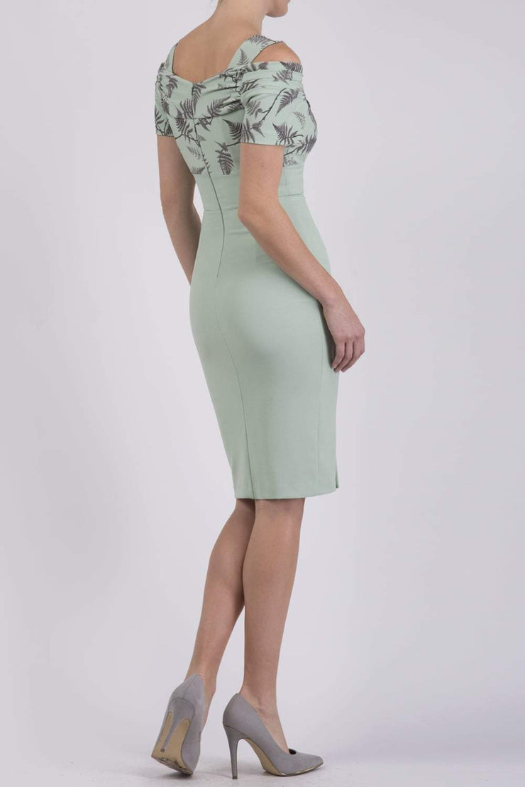 Model wearing the Diva Amorette pencil dress with cold shoulder and pleated detailing on the arms in deco green fern back image