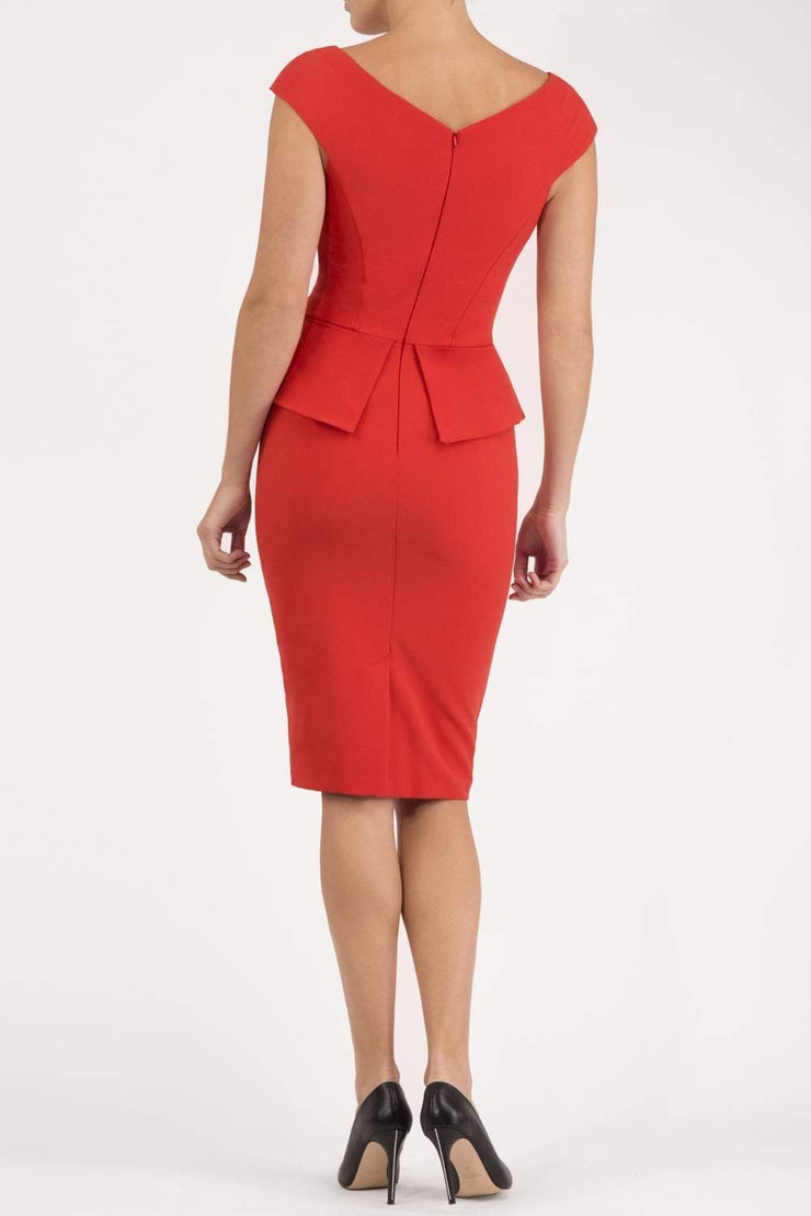 Model wearing the Diva Azalea Peplum dress with semi V neckline and peplum waistline in fiesta orange back image