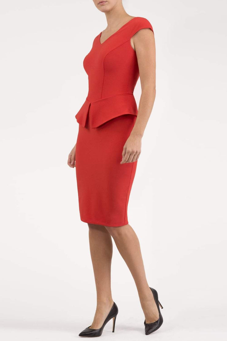 Model wearing the Diva Azalea Peplum dress with semi V neckline and peplum waist detail in fiesta orange front image