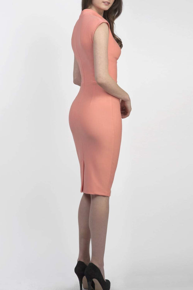 brunette model wearing diva catwalk beyonce pencil fitted dress with high neckline without sleeves with a wide band and pleating across the tummy area with a crossed detail neckline in colour peach back