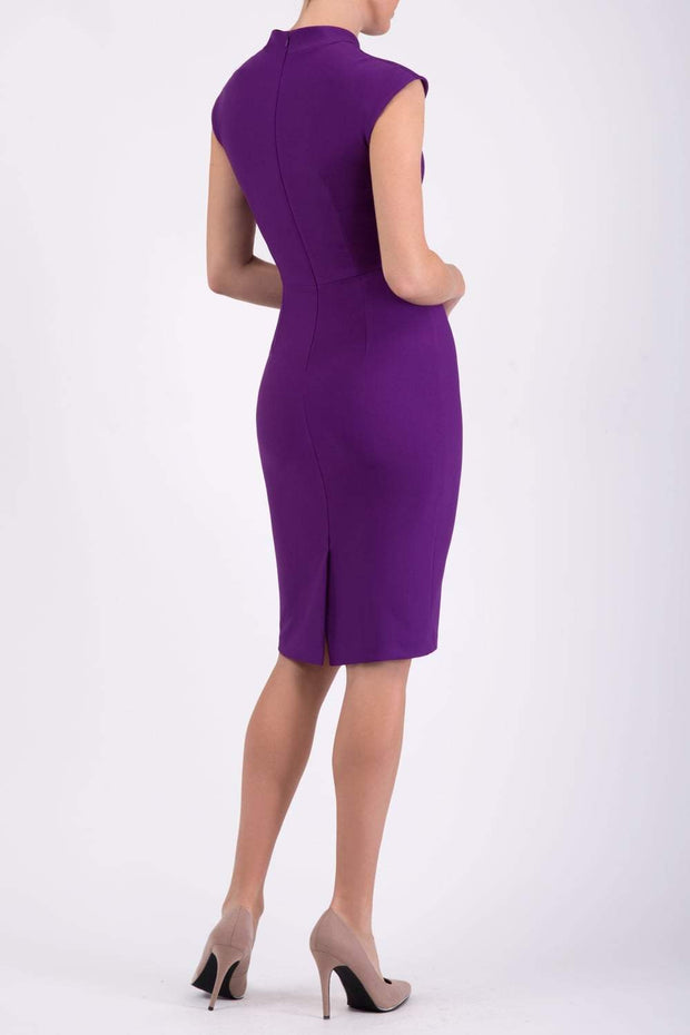 brunette model wearing diva catwalk beyonce pencil fitted dress with high neckline without sleeves with a wide band and pleating across the tummy area with a crossed detail neckline in royal purple back
