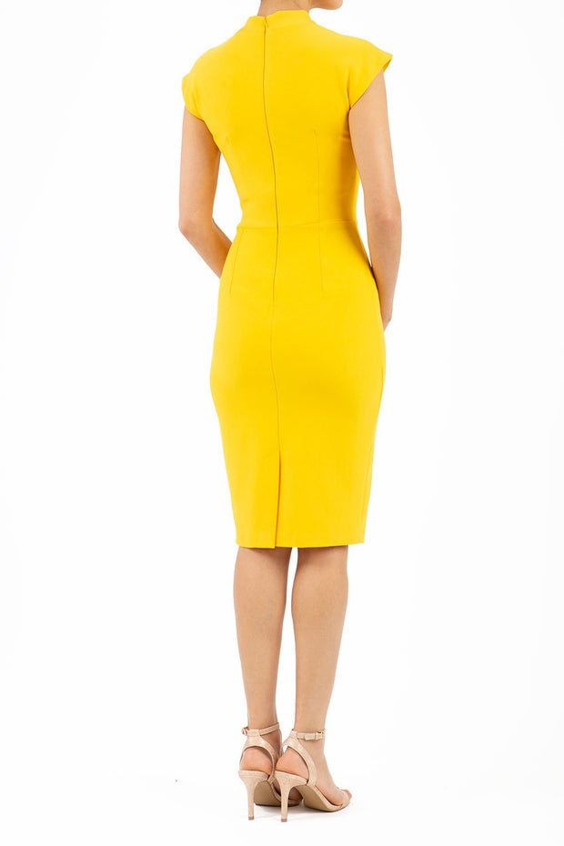 brunette model wearing diva catwalk beyonce pencil fitted dress with high neckline without sleeves with a wide band and pleating across the tummy area with a crossed detail neckline in sunshine yellow back