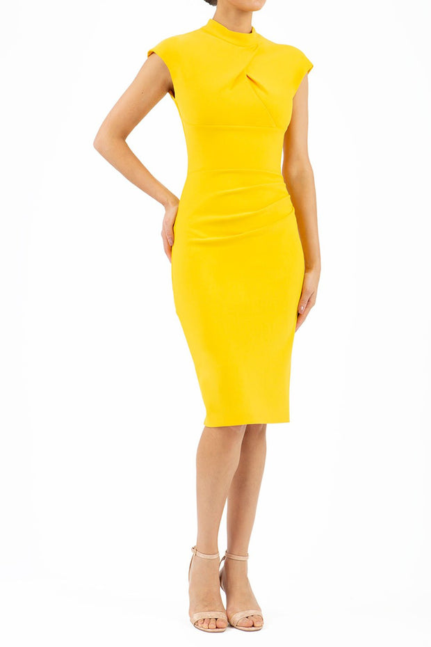 brunette model wearing diva catwalk beyonce pencil fitted dress with high neckline without sleeves with a wide band and pleating across the tummy area with a crossed detail neckline in sunshine yellow front