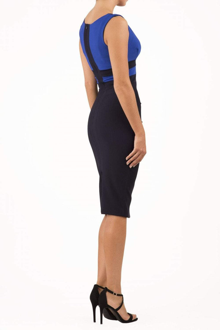 Model wearing the Diva Banbury Colour block dress with bust panels in contrast and pleating across the front in navy blue and cobalt blue front image