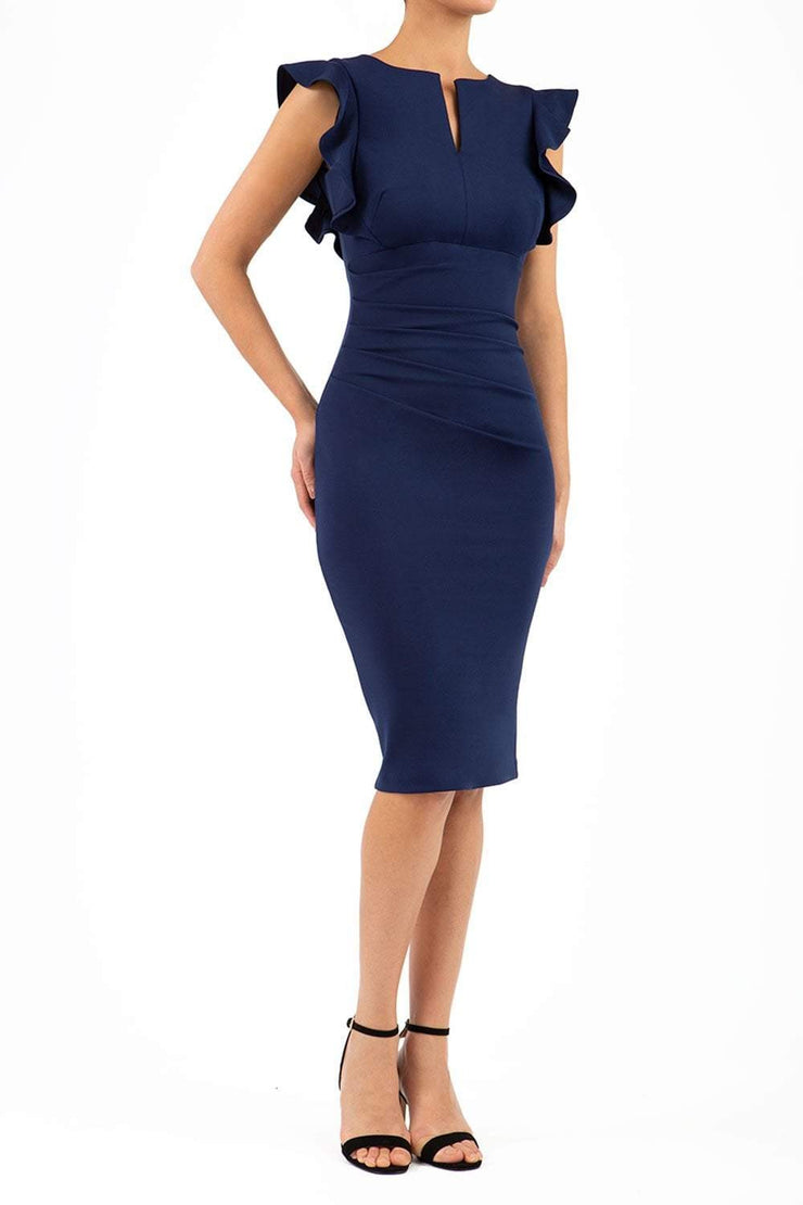 model wearing diva catwalk Bodiam Bodycon Pencil Dress with frill sleeves in knee length and pleating across the tummy in navy front