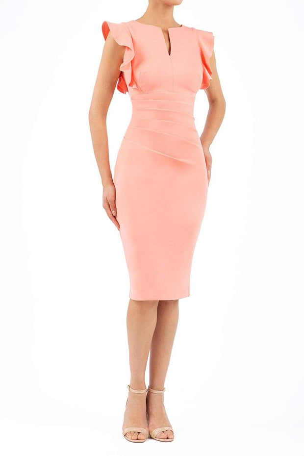 model wearing diva catwalk Bodiam Bodycon Pencil Dress with frill sleeves in knee length and pleating across the tummy in peach front