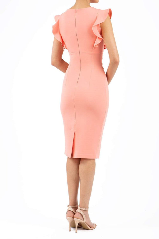 model wearing diva catwalk Bodiam Bodycon Pencil Dress with frill sleeves in knee length and pleating across the tummy in peach back