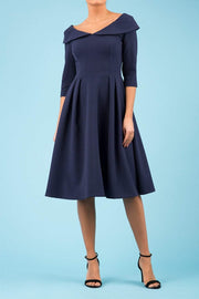 Model wearing Diva Catwalk Chesterton Sleeved dress with oversized collar detail and a-line swing pleated skirt in colour navy front