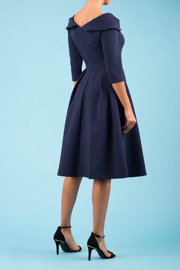 Model wearing the Diva Chesterton Sleeveless dress with oversized collar detail and swing pleated skirt in navy back image