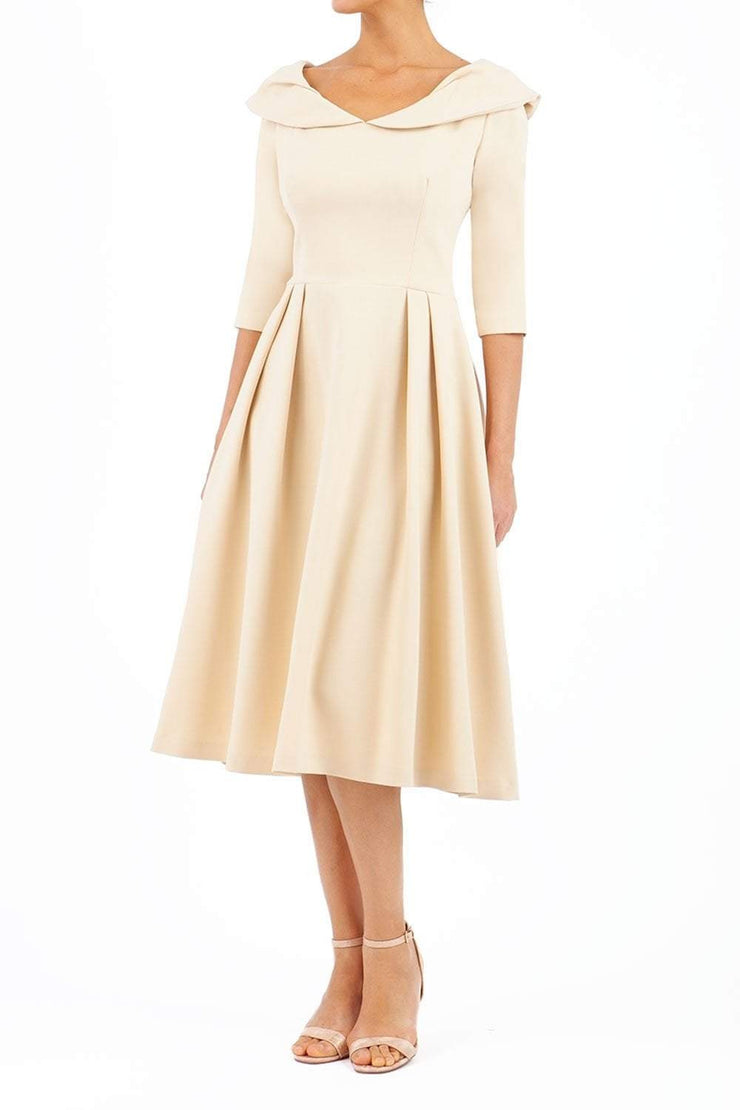 Model wearing the Diva Chesterton Sleeveless dress with oversized collar detail and swing pleated skirt in sandshell beige front image