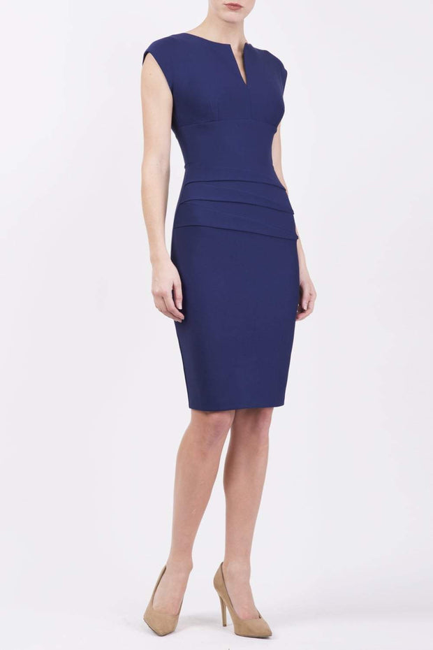 model wearing diva catwalk daphne sleeveless navy blue pencil dress with rounded neckline with split in the middle in front